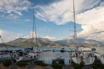 Boats and yachts in the harbor in Gaeta, with mountains and clouds in the background.