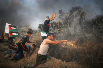 Disabled Palestinian tries to remove Israeli wire during a protest at the Israel-Gaza border fence in Gaza