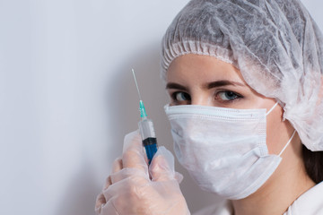 A female doctor in a protective mask holds a syringe in her hand. The nurse is going to make an injection, vaccination.