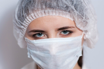Female doctor in a protective mask and cap. Nurse in the treatment room, in the surgical unit.