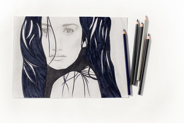 Penciled white and black portrait of brunette girl on paper, pencils on white background top view isolated