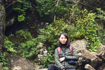 ハイキングの休憩中こちらを見つめる女性