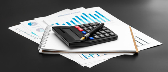 Financial graphs with notepad and calculator on black background.