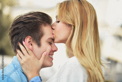 a boy and girl kissing in bed