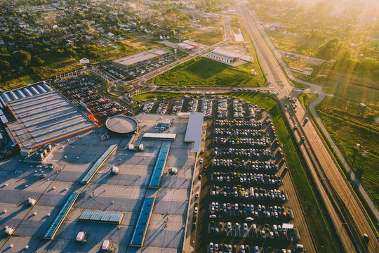 Aerial view of mall and parking with many cars.