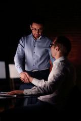 employees shaking hands near the desktop.