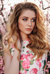 beautiful girl with blond hair in elegant clothes posing in blooming peach garden