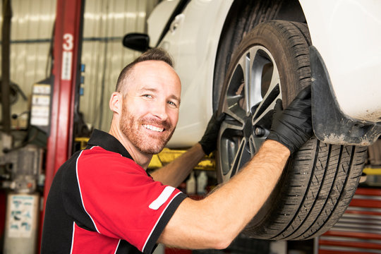 handsome mechanic based on car in auto repair shop