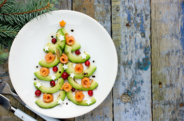 Delicious edible Christmas tree from avocado slices, salty salmon, cranberry and boiled egg stars with balsamic vinegar olive oil dressing on white plate top view