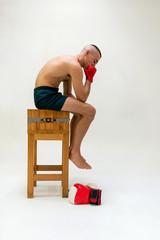 pugile a torso nudo con fasce da boxe e shorts neri su sgabello di legno