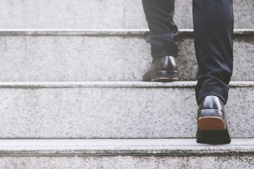 Close up legs shoes of young business man One person walking stepping going up the stairs in modern city, go up, success, grow up. with filter Tones retro vintage warm effect. stairway Fototapete