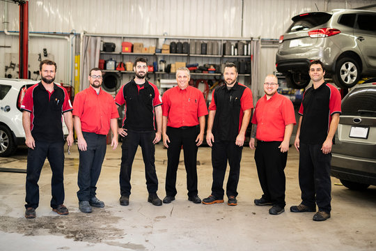Portrait of auto shop mechanics group together employee