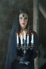 Young woman in a black dress with candles in her hands.