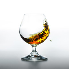 Cognac glass with splashing brandy inside