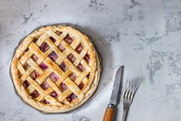 Homemade fruit pie on white stone background.