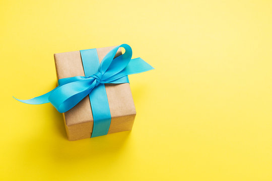 gift wrapped and decorated with blue bow on yellow background with copy space. Flat lay, top view
