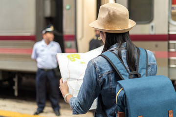 An backpack journalist lady holding map going to asking direction and assistance from a train police in railway train station in Bangkok.