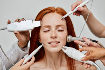 Concept photo of gorgeous happy young ginger woman and beautician hands holding medical maniples for rejuvenating facial procedures for tightening and smoothing wrinkles touching her face.