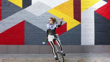Wall Mural - Girl clown with white rose riding a unicycle outdoors