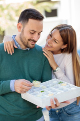 Happy young couple eating snacks in a park. Woman is hugging her boyfriend or husband
