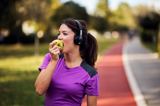 Fitness woman listening music with headphones and eating green apple