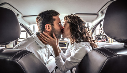 Happy beautiful couple in love kissing in a new car