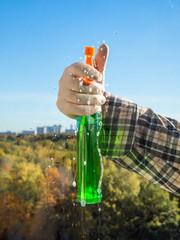 man sprays the washing liquid on glass
