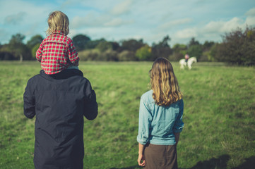 A young family is looking at a horse