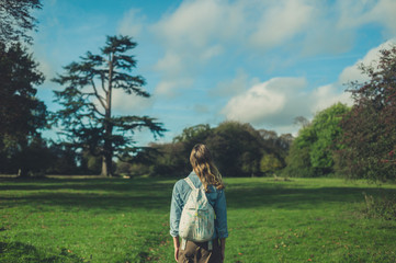 Young woman standing in meadow looking at tree