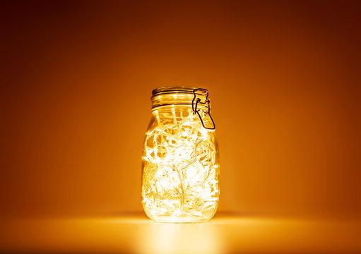 Glass jar with yellow light garland inside, holiday mood