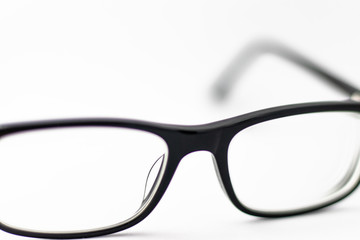 Pair of black glasses lying around on white background