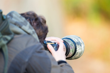 Richmond Park, London. A male photographer using a camera with a large camouflaged lens takes a photograph.