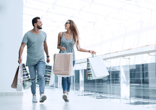 young couple with shopping bags discussing something