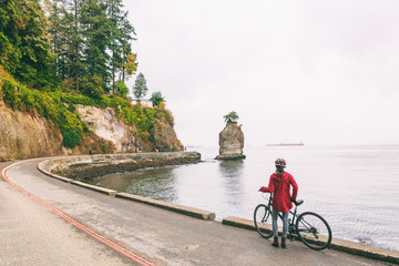 Vancouver cyclist biking woman on bike path around Stanley Park, famous tourist activity in British Columbia, Canada. Fotomurales