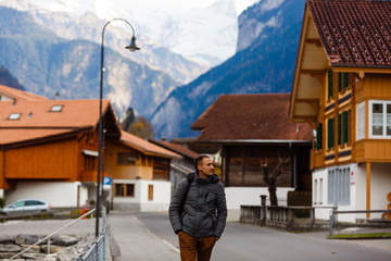 Wall Mural - A man turist looking for a shalet in the Swiss Alps