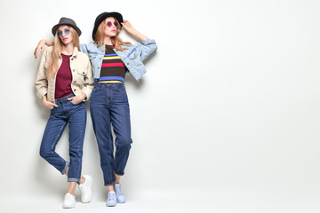 Wall Mural - Two Girl posing in Studio. Young Playful Sisters Having Fun, Trendy Hairstyle, Fashion Stylish jeans, hat. Full-length portrait. Cheerful Blond Redhead Woman in denim Autumn Outfit