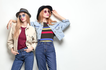 Wall Mural - Two Girl posing in Studio. Young Playful Sisters Twins Having Fun, Trendy Hairstyle, Fashion Stylish jeans, hat. Full-length portrait. Cheerful Blond Redhead Woman in denim Autumn Outfit