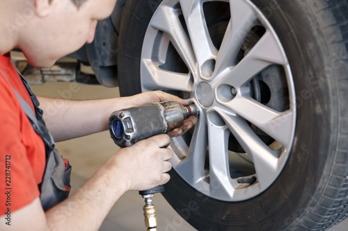 Auto mechanic man with electric screwdriver changing tire