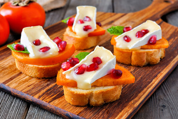 Spoed Fotobehang Voorgerecht Holiday crostini appetizers with persimmons, pomegranates and brie cheese. Close up, side view scene on a wood background.