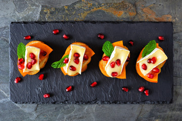 Spoed Fotobehang Voorgerecht Holiday crostini appetizers with persimmons, pomegranates and brie cheese. Overhead view, on a slate server.