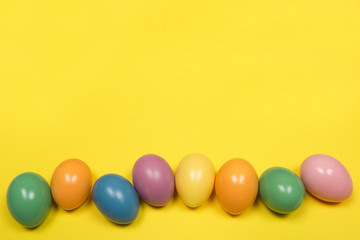 Pastel colored easter eggs on a yellow background with copy space