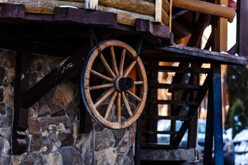 Wooden wheel and a ladder in low light, wood texture, background for creative design