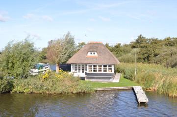 een vakantiewoning met rieten dak in het natuurgebied De Alde Feanen in Friesland