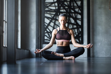 Yoga woman meditating after workout with eyes closed in studio / modern loft near window.