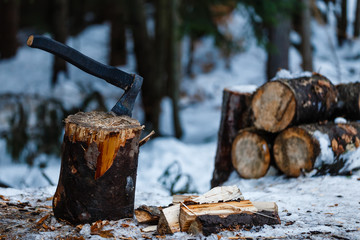 Axe stuck in a log in front of a pile of wood, ready for chopping, wintertime