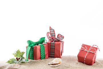 Winter seasonal gift boxes with bow on sand, with white background and copy space.
