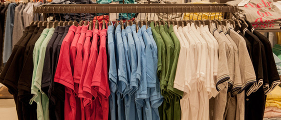 Colorful t-shirts on hangers. Men's stylish clothes. Showcase, sale, shopping. Fashion and trade concept