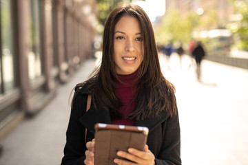 Young woman in city walking using tablet computer