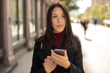 Young woman in city using cell phone walking