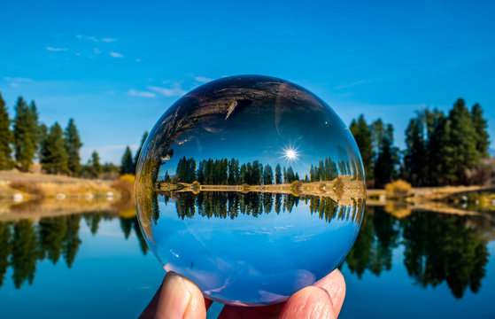A lensball produces an image of a bright sunny blue sky and the reflective beauty of local pond